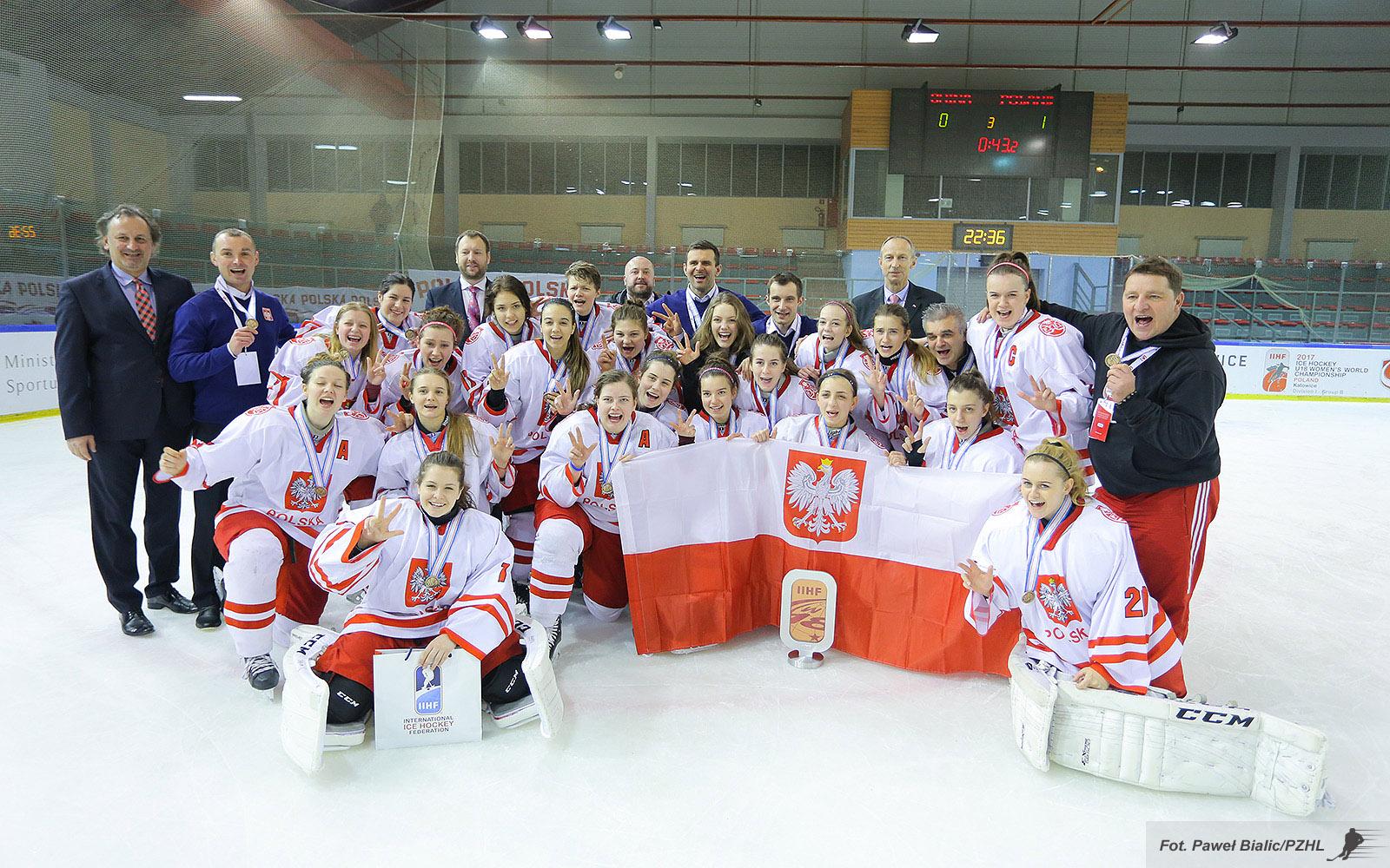 Zawodniczki hokeja w barwach narodowych z flagą, pozują na tafli lodu