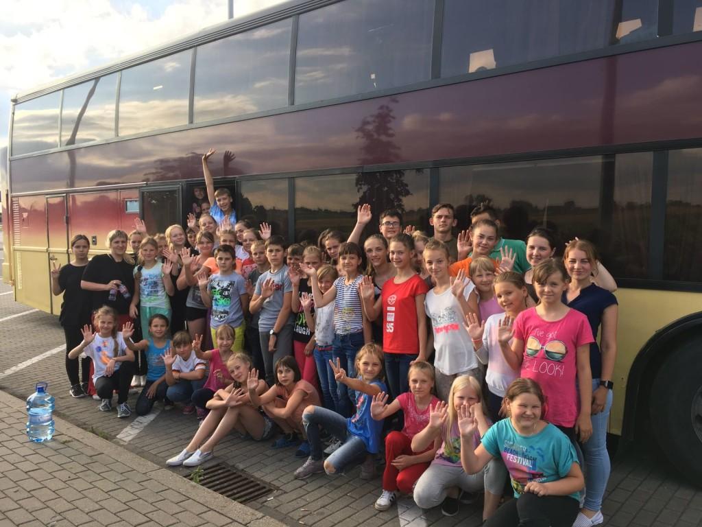 Zdjęcie dzieci stojących przed autobusem
