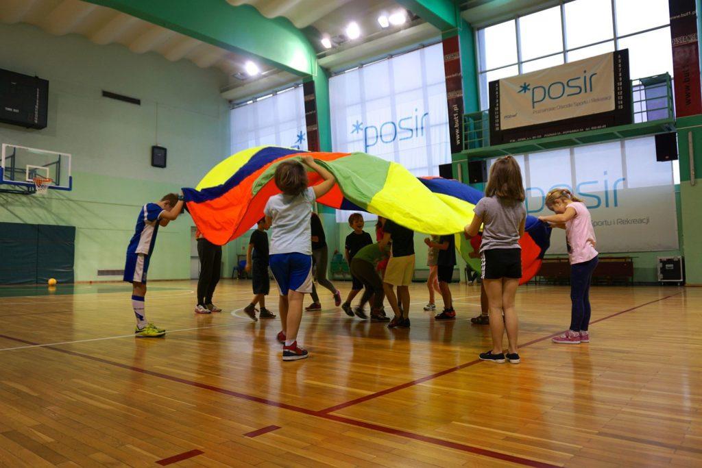 Akcja Zima z POSiR (1) Dzieci bawią się kolorową chustą na sali sportowej