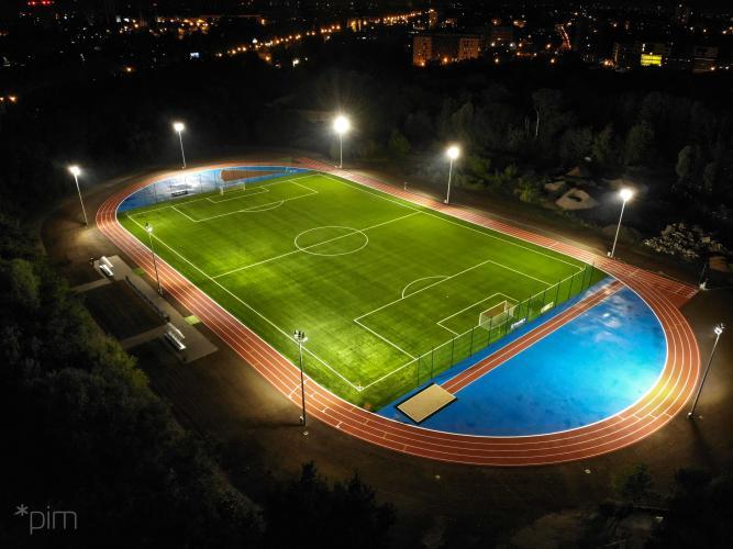 Boisko piłkarskie ze sztuczną nawierzchnią i bieżnią oświetlone w nocy - ujęcie z lotu ptaka