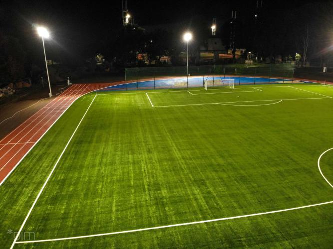 fragment boiska piłkarskiego ze sztuczną nawierzchnią i bieżnią, ujęcie w nocy z lotu ptaka