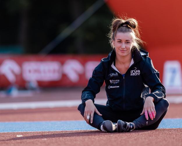 Malwina Kopron siedzi na płycie boiska
