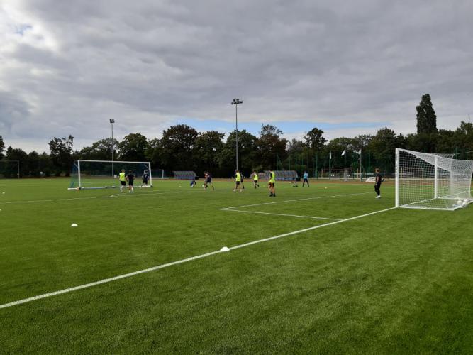 Chłopcy trenują na boisku piłkarskim