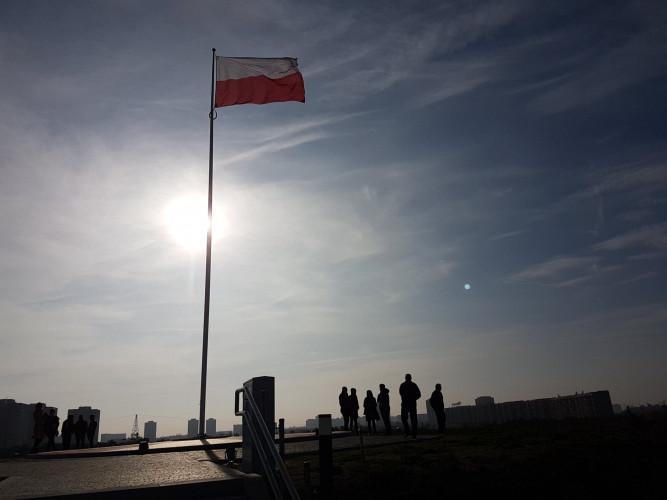 Ludzie na szczycie kopca, maszt z flagą