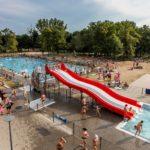 Pływalnia letnia w Parku Kasprowicza (1) Widok ogólny z lotu ptaka - dwa baseny - zjeżdżalnia - tłum ludzi